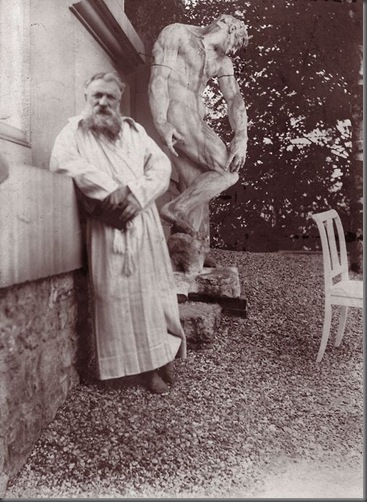 French sculptor Auguste Rodin (1840 - 1917) in the garden of his villa at Meudon, near Paris. Behind him is the original plaster statue of The Creation of Man. Edward Gooch